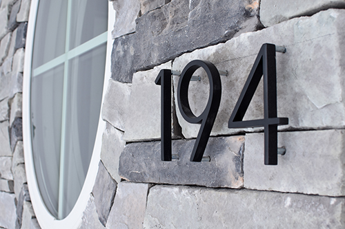 Black 194 numbering on stone veneer with a round white window