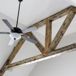 Exposed wooden beams behind a black and white ceiling fan.