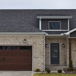 Exterior of brown brick home with a black roof and a brown garage door