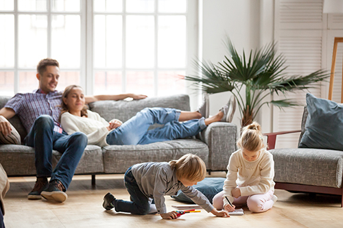 Family gathered in the living room of a new home for sale in Lexington, KY.