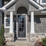 Front walkway leading to front door of a grey and stone home.