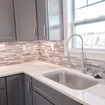 Beautiful kitchen sink with a commercial faucet, grey cabinets, and grey glass tile backsplash.