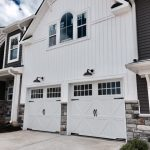 Exterior of a white and stone home with white garage doors.