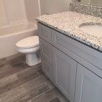 Bathroom vanity with granite countertop and wooden tile flooring.