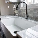 White farmhouse sink with granite countertops in new home construction completed by J Perry Homes.