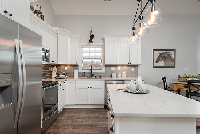 Beautiful white kitchen with wooden flooring and stainless steel appliances.