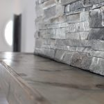 Wooden mantle against a grey stone fireplace.