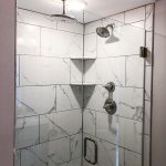 Marble tile shower with glass door and a rainfall showerhead.