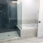 Glass shower with black tile walls next to a large soaking tub and marble flooring.