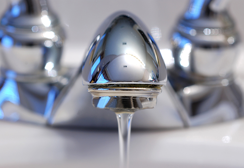 Close up of a silver sink faucet turned on.
