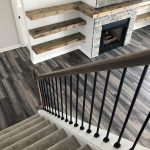 View of looking down carpeted stairs with black railing, looking at a fireplace completed by J Perry Homes, the best home builders in Lexington, KY