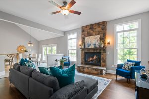 Family room with an open concept floor plan that includes two windows and a stone fireplace.