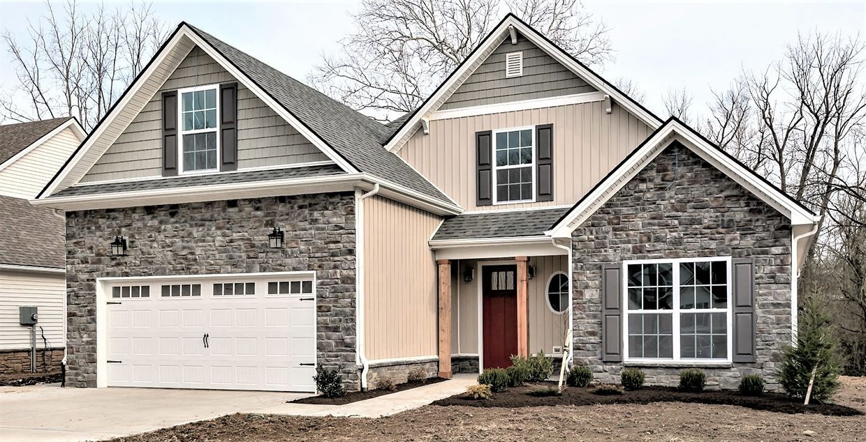 Light grey stone and light tan ship lap exterior on a home built by J Perry Homes