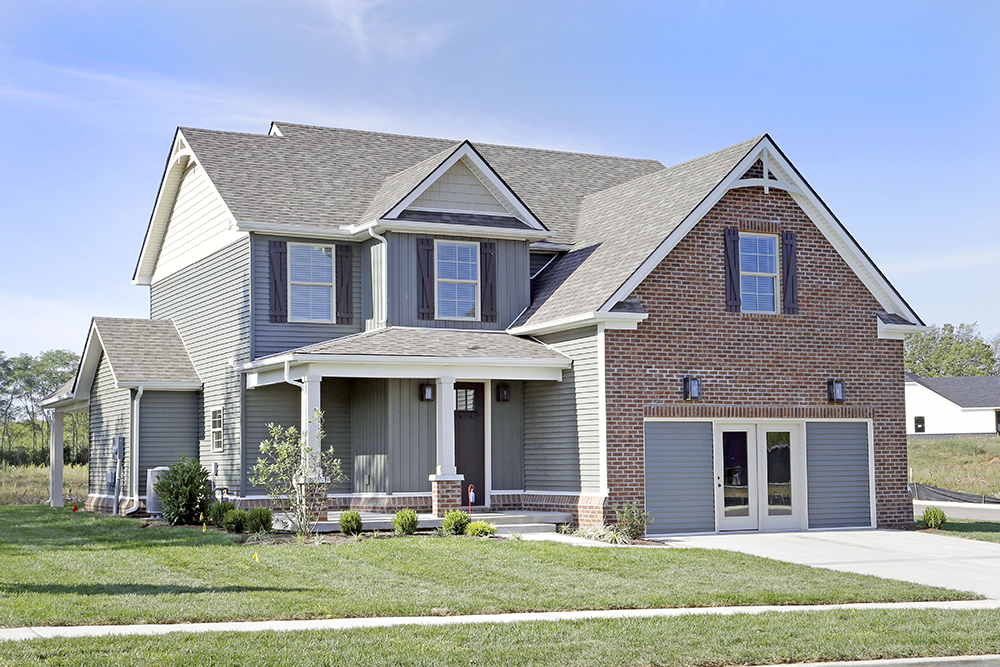 Light brown brick and grey vinyl siding on a home built by home builder J Perry Homes